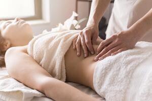 Frau bekommt eine ayurvedische Bauchmassage