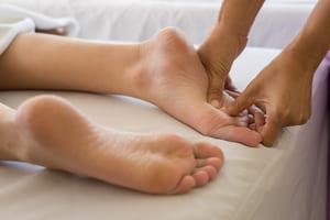 zwei Füße werden mit den Daumen massiert