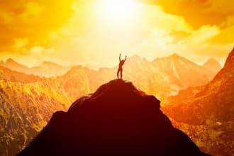 Mensch auf Berg bei Sonnenaufgang