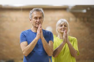 älterer Mann und ältere Frau in Meditationshaltung