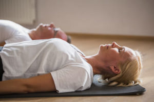 Frau und Mann beim Yoga Nidra in Totenhaltung